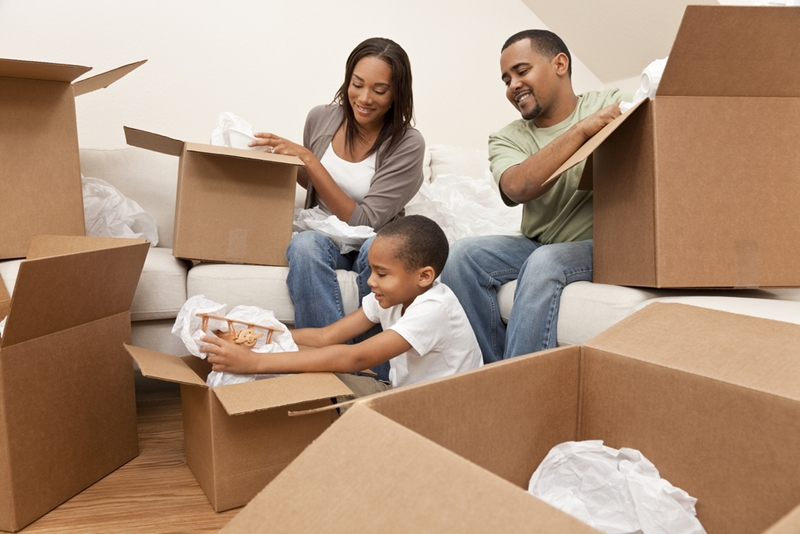 African-American family unpacking moving boxes