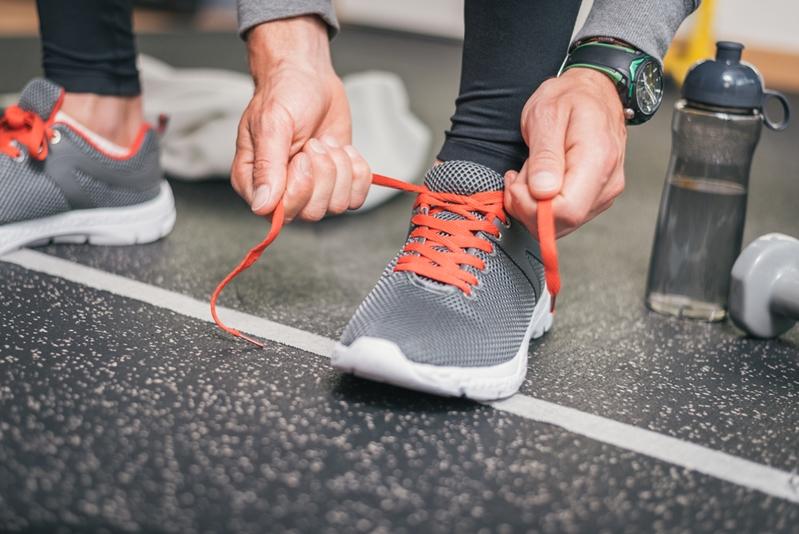 Man tying his gym shoe.